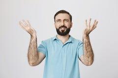 Портрет удовлетворенного бородатого человека держа его ладони вверх изолированный на белой предпосылке Большой, дождь Что_еще мож стоковое фото