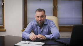 Портрет уживчивого бизнесмена Директор в голубой рубашке сидя на столе офиса, усмехаясь и смотря акции видеоматериалы