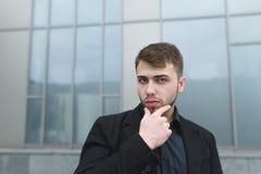 Портрет улицы красивого молодого бизнесмена представляя на камере на предпосылке серой стены стоковое изображение