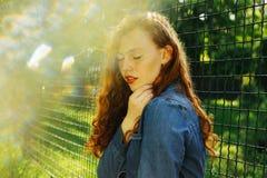 Портрет улицы привлекательной красной с волосами молодой модели представляя в s стоковое изображение