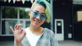 Портрет ультрамодного азиатского жеста рукой и усмехаться ОК показа девушки outdoors видеоматериал