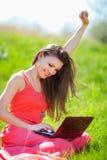 Портрет умной молодой женщины лежа на траве и используя компьтер-книжку Стоковая Фотография