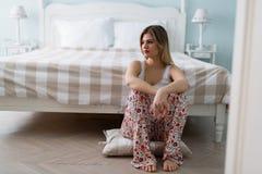 Портрет унылой молодой женщины в спальне Стоковая Фотография