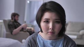 Портрет унылой подавленной азиатской девушки, пьяный супруг на заднем плане сидит в кресле, смотрит в камеру 50 акции видеоматериалы