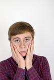 Портрет унылого красивого молодого человека на белой предпосылке стоковое фото