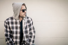 Портрет унылого человека в солнечных очках сидя около дома Стоковые Изображения RF