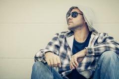 Портрет унылого человека в солнечных очках сидя около дома Стоковое Изображение RF