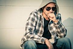 Портрет унылого человека в солнечных очках сидя около дома Стоковые Фото