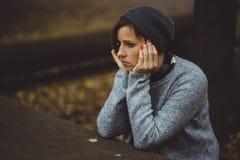 Портрет унылой женщины сидя самостоятельно в концепции уединения леса Millenial общаясь с проблемами и эмоциями Стоковое фото RF