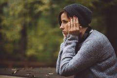 Портрет унылой женщины сидя самостоятельно в концепции уединения леса Millenial общаясь с проблемами и эмоциями Стоковые Фото