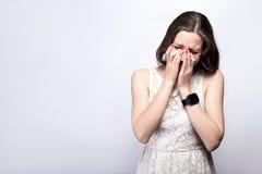 Портрет унылой, несчастной плача женщины с веснушками и платьем белизны и умным вахтой на предпосылке серебряного серого цвета Стоковые Изображения RF