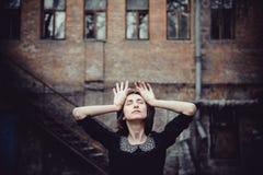 Портрет упадочной эмоциональной девушки стоя около старого здания с окнами Винтажный тон, унылая депрессия, насилие, двухполярное Стоковое Фото