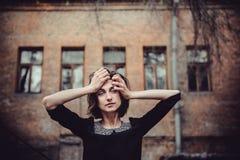 Портрет упадочной эмоциональной девушки стоя около старого здания с окнами Винтажный тон, унылая депрессия, насилие, двухполярное Стоковая Фотография RF