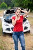 Портрет усиленной молодой женщины стоя на ее сломленном автомобиле и вызывая обслуживание автомобиля Стоковое Изображение RF