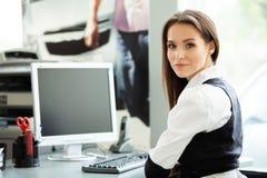 Портрет усмехаться довольно молодая бизнес-леди сидя на рабочем месте стоковое изображение rf