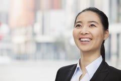 Портрет усмехаться, уверенно, молодая коммерсантка конца-вверх при ponytail смотря вверх, outdoors с небоскребами в backgrou Стоковая Фотография RF