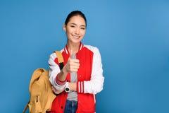 портрет усмехаясь азиатского студента показывая большой палец руки вверх стоковое изображение