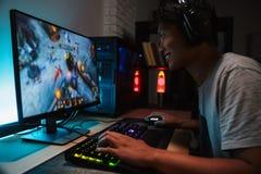 Портрет усмехаясь азиатское видеоигр мальчика 16-18 gamer играя дальше стоковое фото