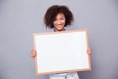 Портрет усмехаясь афро американской женщины держа пустую доску Стоковое Изображение