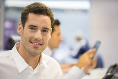 Портрет усмехаясь бизнесмена в офисе, смотря камеру Стоковые Изображения