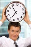 Портрет усмехаясь бизнесмена держа часы к его голове Стоковое Изображение