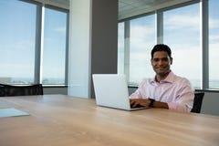Портрет усмехаясь бизнесмена используя компьтер-книжку в конференц-зале Стоковая Фотография RF