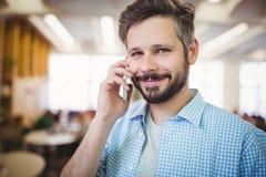 Портрет усмехаясь бизнесмена используя телефон в столовой Стоковые Изображения RF