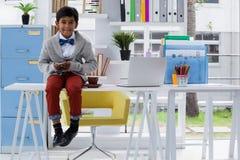 Портрет усмехаясь бизнесмена используя телефон пока сидящ на столе Стоковые Фотографии RF