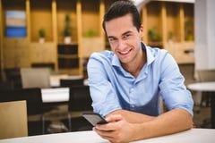 Портрет усмехаясь бизнесмена используя телефон Стоковые Фото