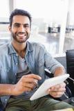 Портрет усмехаясь бизнесмена используя цифровую таблетку пока сидящ на кресло-коляске Стоковые Изображения