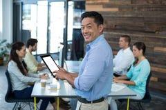 Портрет усмехаясь бизнесмена используя цифровую таблетку Стоковые Фото