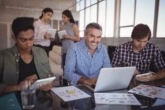 Портрет усмехаясь бизнесмена работая на компьтер-книжке на творческом офисе Стоковая Фотография RF