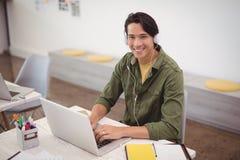 Портрет усмехаясь бизнесмена работая над компьтер-книжкой на столе пока носящ наушники Стоковое Изображение RF