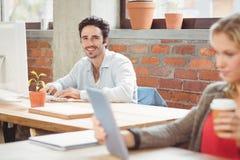 Портрет усмехаясь бизнесмена работая на компьютере Стоковая Фотография RF