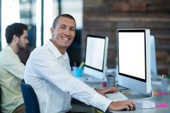 Портрет усмехаясь бизнесмена работая на персональном компьютере Стоковое Изображение