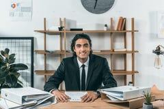 портрет усмехаясь бизнесмена смотря камеру пока сидящ на рабочем месте Стоковые Изображения RF