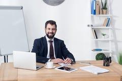 портрет усмехаясь бизнесмена смотря камеру пока сидящ на рабочем месте Стоковое Изображение