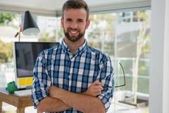 Портрет усмехаясь бизнесмена стоя в офисе Стоковое Фото