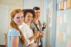 Портрет усмехаясь бизнесменов готовя стеклянную стену Стоковое фото RF