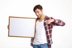 Портрет усмехаясь вскользь парня указывая палец Стоковые Фото