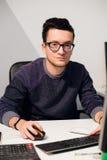 Портрет усмехаясь вскользь бизнесмена работая с компьютером в офисе Стоковое Изображение