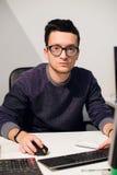 Портрет усмехаясь вскользь бизнесмена работая с компьютером в офисе Стоковые Фото