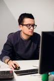 Портрет усмехаясь вскользь бизнесмена работая с компьютером в офисе Стоковые Фотографии RF