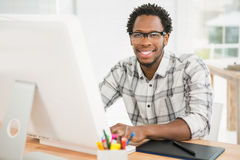 Портрет усмехаясь вскользь бизнесмена работая с компьютером и смотря камеру Стоковые Фотографии RF