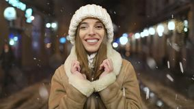 Портрет усмехаясь девушки вечером во время снежностей акции видеоматериалы