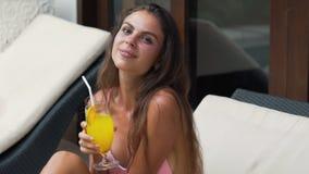Портрет усмехаясь девушки в купальнике держит стекло с соком в руках, смотря камеру, замедленное движение видеоматериал