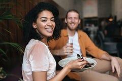 Портрет усмехаясь девушки сидя в ресторане с другом Славная Афро-американская дама сидя на кафе с плитой  Стоковые Фотографии RF