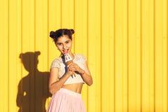 Портрет усмехаясь девушки с мороженым в руках на желтом b стоковые фото