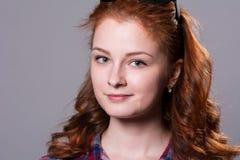 Портрет усмехаясь девушки с солнечными очками на голове смотря камеру Стоковое Фото
