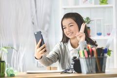 Портрет усмехаясь девушки указывая палец вверх и принимает фото Стоковая Фотография RF